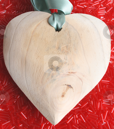 Heart stock photo, Large wooden heart on a bed of red beads by Vanessa Van Rensburg