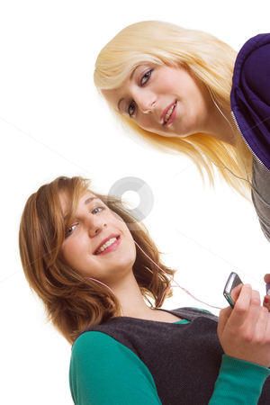 Smiling girls stock photo, Two smiling teenager girls listening their music players by Mikhail Lavrenov