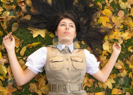 Lying on golden leaves stock photo, Pretty brunette girl resting in an autumn park by Mikhail Lavrenov