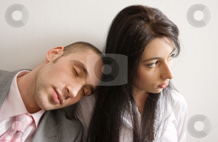 Overtime stock photo, Young man and woman leaning against the wall; man is sleeping on woman's shoulder by Mikhail Lavrenov
