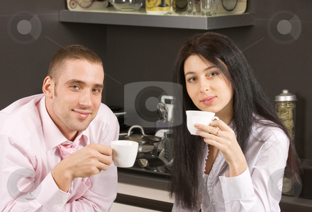 Morning coffee stock photo, Young adult couple having their coffee in the kitchen by Mikhail Lavrenov