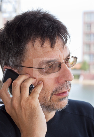Listening attentively stock photo, Close-up portrait of a mature man speaking on cellphone by Mikhail Lavrenov