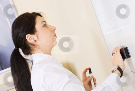 Pretty brunette girl cleaning whiteboard stock photo, Pretty brunette girl cleaning whiteboard during presentation by Mikhail Lavrenov