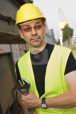 Worker stock photo, Worker with adjustable wrench standing next to a large machine by Mikhail Lavrenov