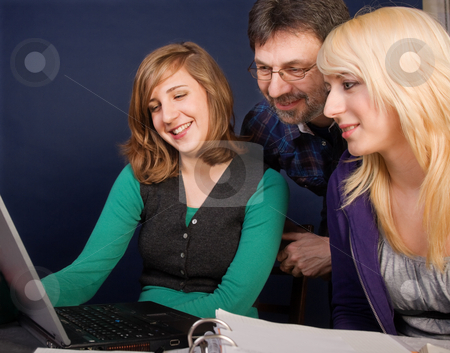 Happy family stock photo, Smiling teenager girls and their father looking at laptop screen by Mikhail Lavrenov