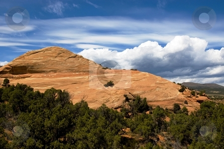 Petrified Dune stock photo, Small hill of red sandstone with bright clouds behind. by Andrew Orlemann