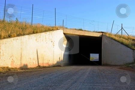 Tunnel stock photo, Square tunnel under a highway along a gravel road. by Andrew Orlemann