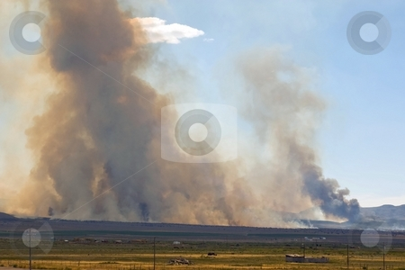 Wildfire Approaches stock photo, Wildfire with dark smoke burning near some outbuildings. by Andrew Orlemann