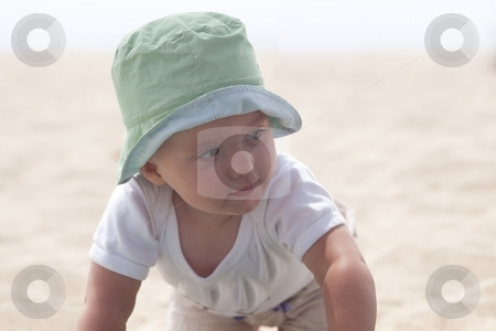 Playing on sand stock photo, Cute Caucasian baby girl playing with the sand on the beach. by Mariusz Jurgielewicz