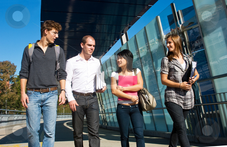 Walking to class stock photo, Four university students walking to class over a modern bridge on a beautiful sunny day by Corepics VOF
