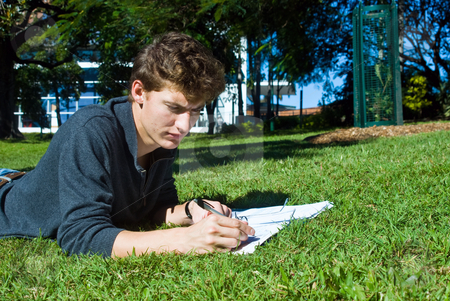 Homework in the park stock photo, Young college student doing his homework in the park on a sunny day by Corepics VOF
