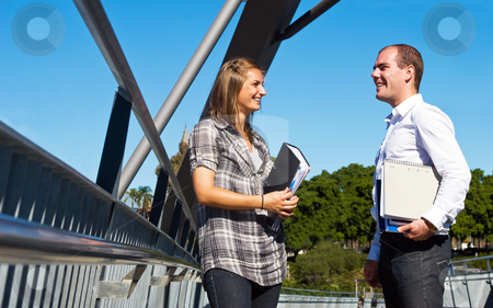 Students stock photo, Two university students talking on their way to classes, holding their books and notes by Corepics VOF