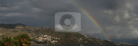 Rainbow stock photo, A panoramic landscape with mountains, moody sky and rainbow.  Castle in extreme right. by Darren Booth