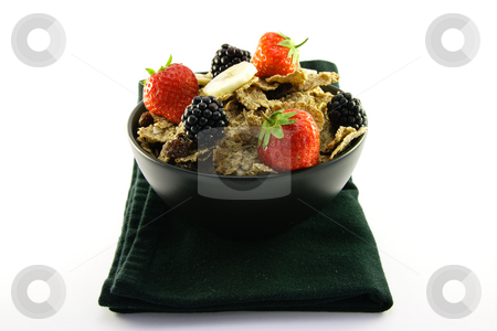 Bran Flakes in a Black Bowl stock photo, Crunchy looking delicious bran flakes and juicy fruit in a black bowl on a black napkin on a white background by Keith Wilson
