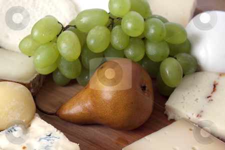 Pear, Cheese and grape stock photo, Wooden plate with fruits and several kinds of cheese and bread by Fabio Alcini