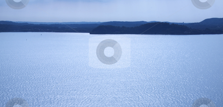 Lansdscape of lake stock photo, Blue landscape of lake with dark mountains in the background by Fabio Alcini