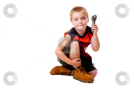 Boy with wrench stock photo, Cute young boy holding toy wrench while sitting, isolated. by Paul Hakimata