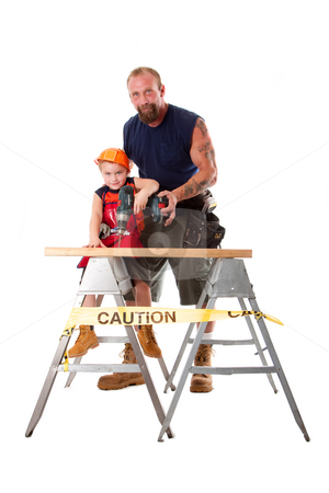 Father teaching son drilling stock photo, Caucasian dad is teaching cute son with construction helmet how to drill a hole in a wooden plank, isolated. by Paul Hakimata