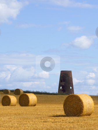 Old windmill 3 stock photo, An old weathered windmill in a field of wheat at harvest time in summer by Mike Smith
