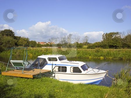 Pleasure boat stock photo, A sailing boat moored by a river bank in summer by Mike Smith