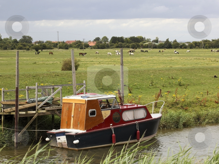 Small boat on river hull stock photo, A small boat on the river hull with fields and livestock in summer by Mike Smith