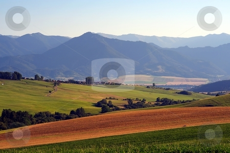 Brown field stock photo, Brown field and green meadows with mountains in background by Juraj Kovacik