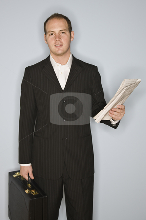 Man with Briefcase stock photo, A young man is holding a briefcase and a newspaper, and is smiling at the camera.  Vertically framed shot. by Jonathan Ross