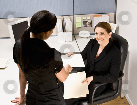 Businesswoman handing co-worker file folder stock photo, Businesswoman handing co-worker file folder by Jonathan Ross