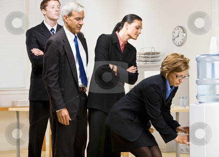 Business people waiting turn at water cooler stock photo, Business people waiting turn at water cooler by Jonathan Ross