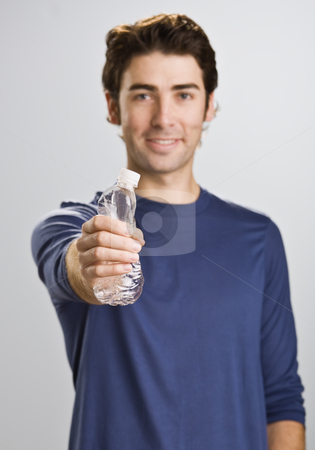 Man Crushing Water Bottle stock photo, A young man is standing in a room and cushing a water bottle.  He is smiling at the camera.  Vertically framed shot. by Jonathan Ross
