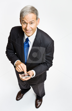 Businessman text messaging on cell phone stock photo, Businessman text messaging on cell phone by Jonathan Ross