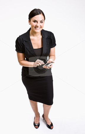 Businesswoman text messaging on cell phone stock photo, Businesswoman text messaging on cell phone by Jonathan Ross