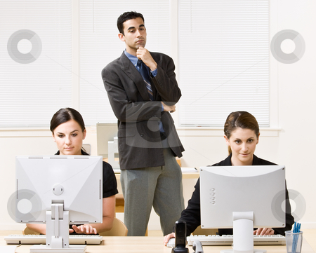Businessman watching co-workers work stock photo, Businessman watching co-workers work by Jonathan Ross