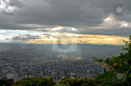 Sunset over Bogota stock photo, Beautiful sunset over Bogota, with sunbeams breaking through the cloud cover illuminating the center of the city. The picture was taken from the Monserrate. by Tijs Zwinkels