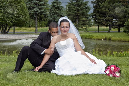 Married couple stock photo, Just married multi ethnic couple sitting in the grass by Vlad Podkhlebnik
