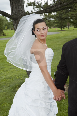 Married couple stock photo, Just married bride looking behind her by Vlad Podkhlebnik