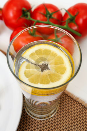 Glass Of Lemon Water stock photo, Glass of cold water with a slice of fresh lemon for a refreshing flavor. by Lynn Bendickson