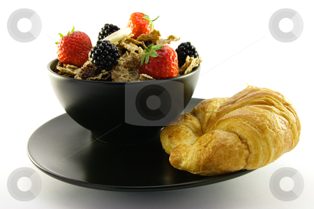 Bran Flakes in a Black Bowl stock photo, Crunchy looking delicious bran flakes and juicy fruit in a black bowl with a croissant on a white background by Keith Wilson