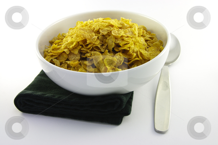 Cornflakes in a Bowl with a Spoon stock photo, Golden crisp cornflakes in a round white bowl with a black napkin and a spoon on a white background by Keith Wilson