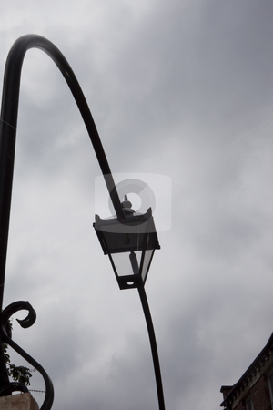 Traditional lamp against a grey sky stock photo, Traditional black metal exterior lamp on metal arch against a grey cloudy sky by Mike Smith