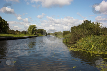 Waterway stock photo, A view along a canal with a blue summer sky reflected in the water by Mike Smith