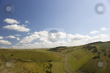 Summer sky over green hillside stock photo, A blue summer sky with white clouds over hillside pastures by Mike Smith