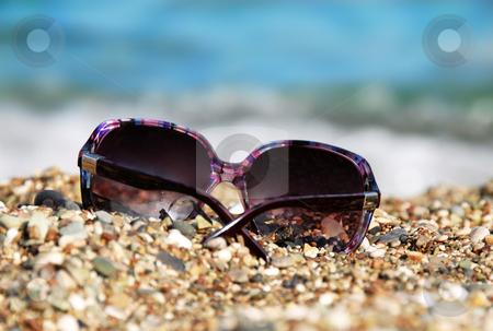 Sunglasses in pebble stock photo, Purple plastic sunglasses in pebble over blue sea by Julija Sapic