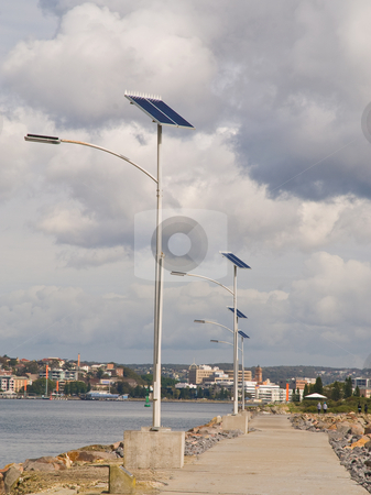 Path lit by solar power stock photo, Row of solar powered street lights lining path along the water with city in the background by Emma White