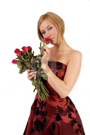 Woman smelling roses stock photo, Blond woman is a red cocktail dress is smelling roses by Daniel Kafer