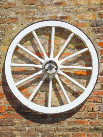 Old cart wheel stock photo, An old cart wheel on a brick wall in summer by Mike Smith