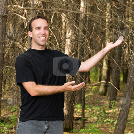 Save The Trees stock photo, A young man standing in a forest with his arms showing off the trees by Richard Nelson