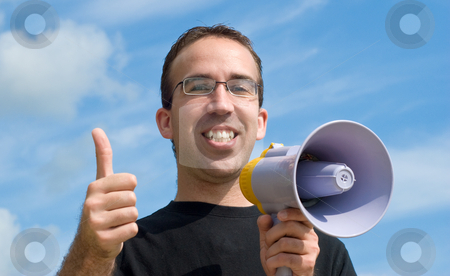 Thumbs Up stock photo, A young man holding a megaphone giving a thumbs up signal, with blue sky and clouds behind him by Richard Nelson