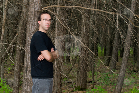 Man Standing In The Forest stock photo, A young man standing in the forest with copyspace to the right by Richard Nelson