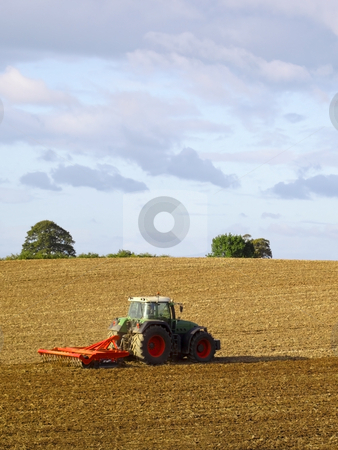 A tractor cultivating stock photo, A tractor cultivating a field under a summer sky by Mike Smith